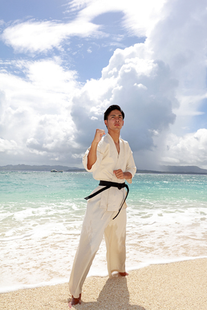 Young man practicing karate at the beach