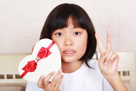 彼女の手に贈り物を持ってうれしそうな女の子 写真素材