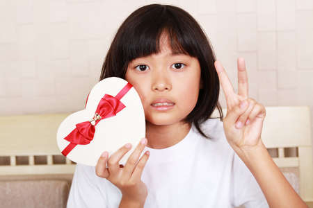 彼女の手にギフトを持ってうれしそうな女の子 写真素材