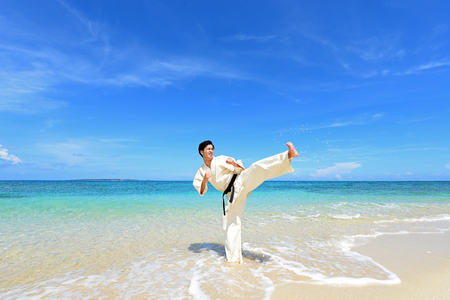Young adult man with black belt practicing a Kata on the beach on a sunny day.