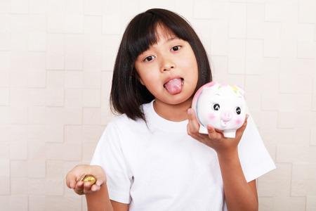 Smiling Asian girl with a Piggy bank 版權商用圖片