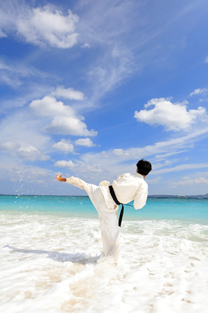 Man practicing karate at the beach