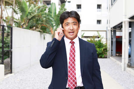 Businessman who is talking on a smart phone Stock Photo