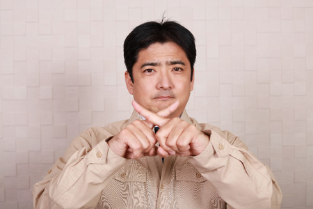 Asian worker demonstrating prohibiting gesture