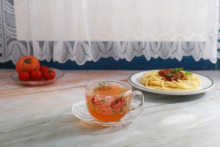 A cup of tea with spaghetti on the table. Reklamní fotografie