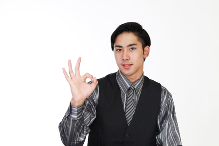 Smiling Asian waiter with ok hand sign Banco de Imagens