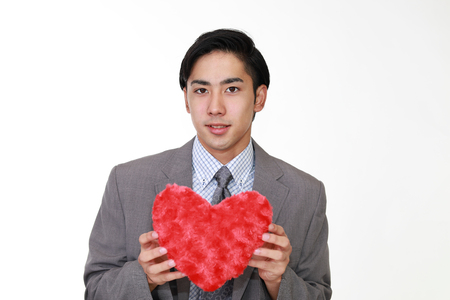 Smiling man holding red heart love symbol