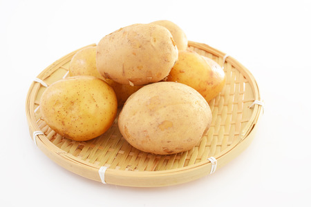 Fresh potatoes on a bamboo tray 写真素材