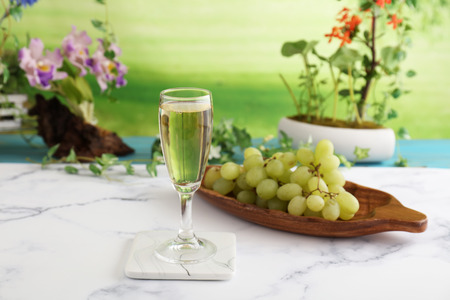 A glass of white wine and grapes