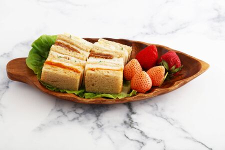 Fresh and tasty sandwiches on a wooden plate