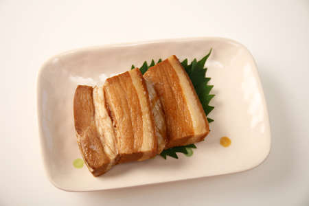 Okinawan cuisine, Pork dish on the plate. 免版税图像