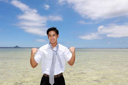 Smiling Asian man on the beach. 免版税图像