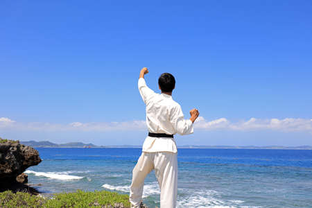 A man practicing karate at the beach.