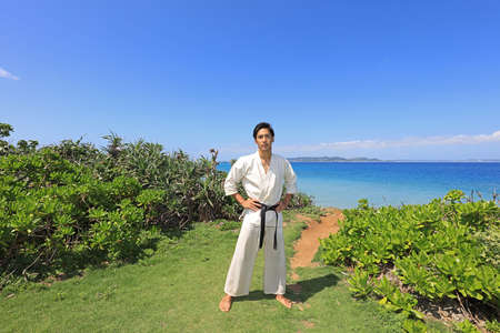 Young man practicing karate by the sea.