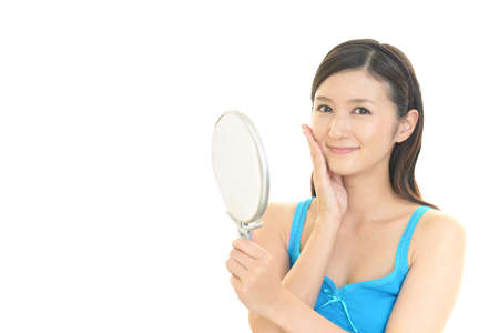 Asian woman looking at her face in mirror. 免版税图像