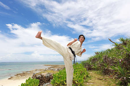 Young man with black belt practicing a Kata on the beach.