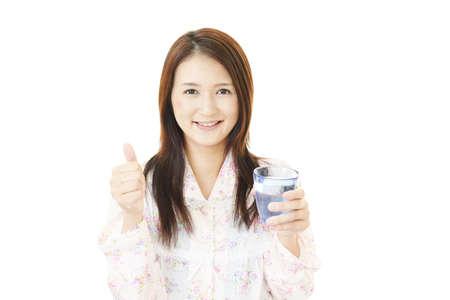 Woman drinking a glass of water. 免版税图像