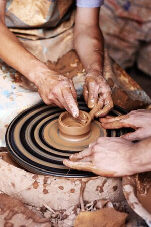 slavs: Potter teaches to sculpt in clay pot on a turning pottery wheel Stock Photo