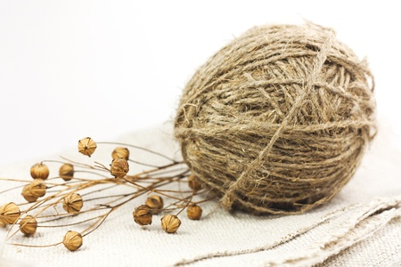 A ball of flax yarn and flax are on linen