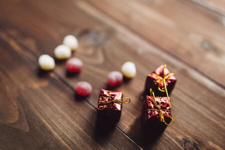 sweeties: Heart shaped sweeties with Christmas gifts on the wooden background