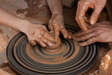 sculpt: Potter teaches to sculpt in clay pot on the turning pottery wheel