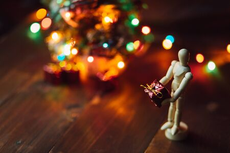 hinged: Wooden hinged Mannequin with the gift and the Chritsmas tree on the wooden table Stock Photo