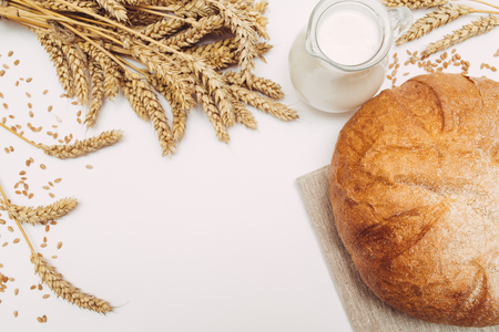 Jug of milk, wheat and fresh homemade bread on white background isolated with copy space