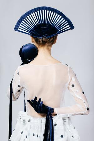 velvet dress: Shot of Japanese young woman in fashion elegant designers diaphanous dress and blue velvet gloves, back Stock Photo
