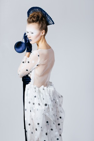 velvet dress: Creative shocking portrait of Japanese young woman in fashion elegant designers grey dress and blue velvet gloves on grey blackground Stock Photo