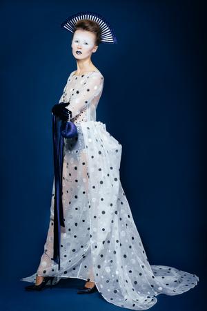 velvet dress: Full body shot of Japanese young woman in fashion elegant designers grey dress and blue velvet gloves on blue blackground