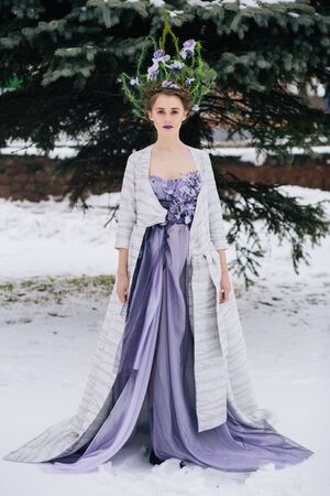 seductress: Outdoor full body shot of beautiful young woman in fashion elegant designer purple dress with crown in winter Stock Photo