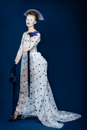 velvet dress: Full body shot of Japanese young woman in fashion elegant designers grey dress and blue velvet gloves on blue blackground