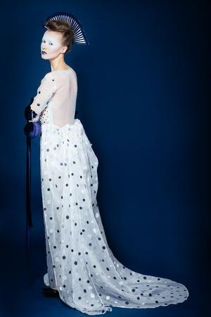 blue velvet: Full body shot of Japanese young woman in fashion elegant designers grey dress and blue velvet gloves on blue blackground