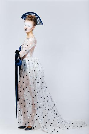 velvet dress: Full body shot of Japanese young woman in fashion elegant designers grey dress and blue velvet gloves on grey blackground
