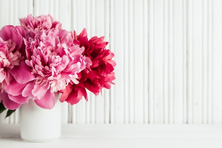 Fresh peonies flowers in white vase on white wooden background, copy space, selective focus