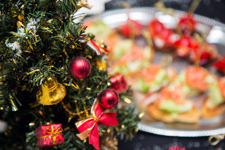Christmas tree and buffet table full of canape with salmon, olives and fresh red pepper, Christmas snacks. Food for holiday table