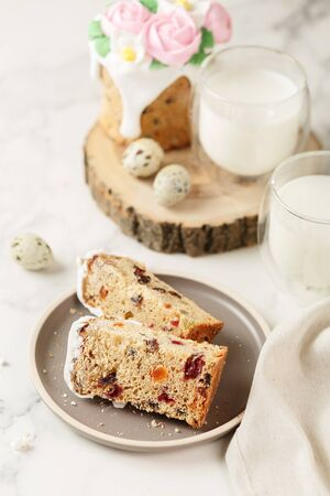 Slices of Easter cake with raisins and dried apricots. Homemade pie with a glass of milk. Piece of cake with marzipan floral decoration on plate. Holiday breakfast and cooking concept.