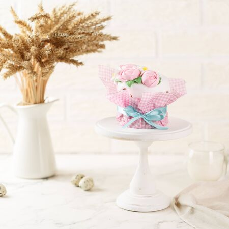 Easter cake in pink paper packaging with blue ribbon on the grey plate. Homemade festive pie with frosting and mastic floral decoration. Bunch of wheat ears at the background. Happy Easter concept. Copy space