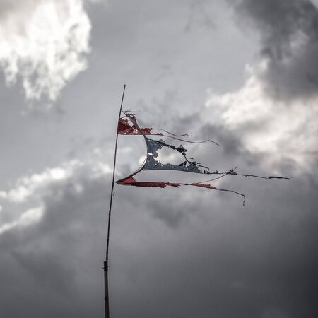 strom: thai torn flag fluttering in the wind, posted signs on a rusty pole, before strom Stock Photo