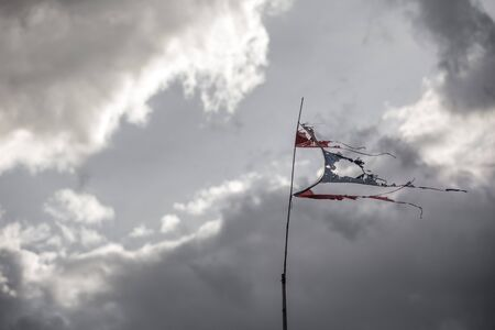 posted: thai torn flag fluttering in the wind, posted signs on a rusty pole, before strom Stock Photo