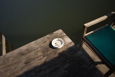 ashtray: used white ashtray on wood table