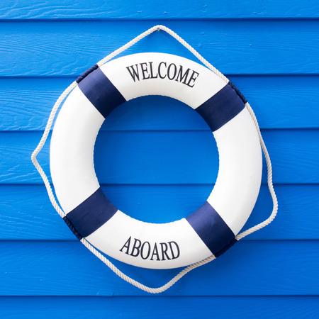 the welcome: Boya de vida blanca con la bienvenida a bordo en la pared azul