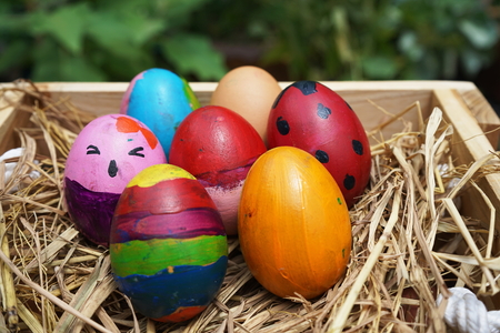 Easter concept, many fancy colorful Easter eggs in wooden nest box Stock Photo