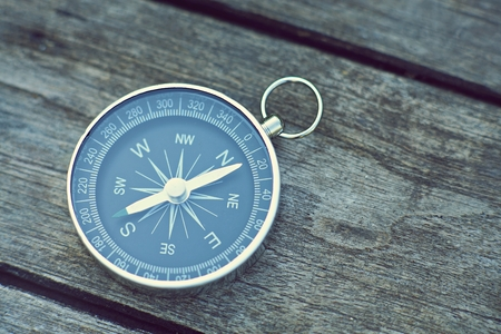 Compass on old wooden table background, journey planning concept, vintage tone Stok Fotoğraf