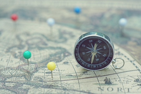 Compass and marking pins on blur vintage map, journey planning concept 写真素材