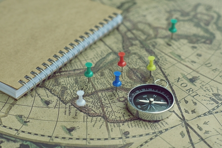 Compass and notebook on blur vintage world map, journey concept, copy space 写真素材