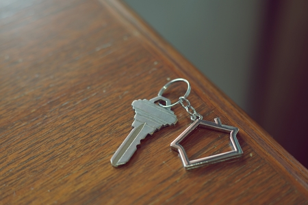 Home key with metal house keychain on wooden table, property concept