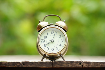 Analog alarm clock on wooden table with blur green garden background, 8 am., 8 oclock, copy space Banco de Imagens