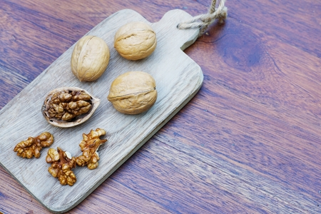 Group of walnuts and a crack nut in wooden bowl on wood background, copy space, super food concept Imagens