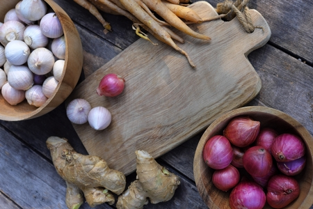 Top view of wooden table full of herbal vegetable ingredients, garlic, red onion, finger root, ginger, copy space, food concept